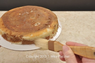 Brushing crumbs from side of cake