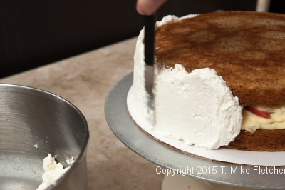 Spreading cream over side of cake