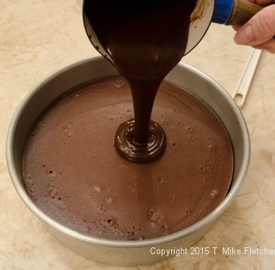 Glaze being poured onto the Triple Chocolate Cheesecake