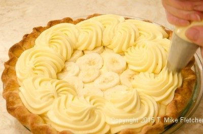 Piping the pastry cream over the bananas for the Double Banana Caramel Cream Pie