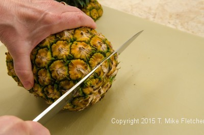 Cutting the bottom of the pineapple off for the Pina Colada Cake