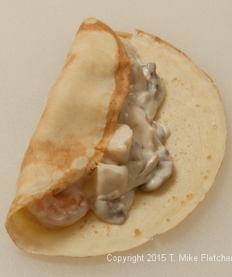 Left side of crepes folded over for Seafood Crepes