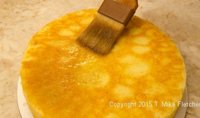Soaking cake with rum syrup for The Pina Colada Cake