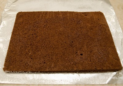 Spongecake turned out on powdered sugar foil for Buche de Noel