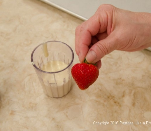 Holding strawberry to dip for the Chocolate Strawberry Ruffle Cake