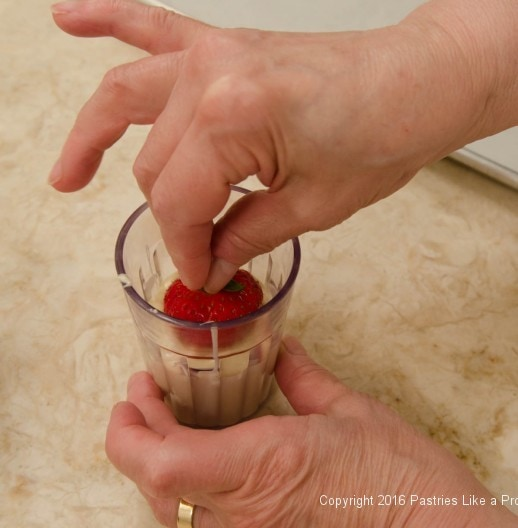 Dipping a strawberry into chocolate for the Chocolate Strawberry Ruffle Cake