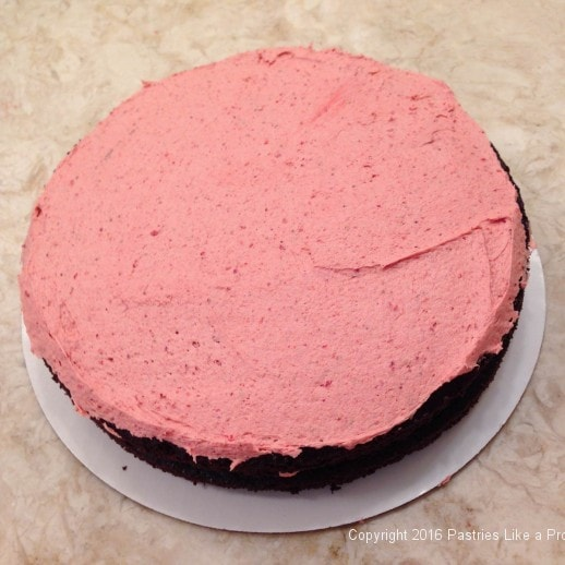 Filling first layer of cake for the Chocolate Strawberry Ruffle Cake