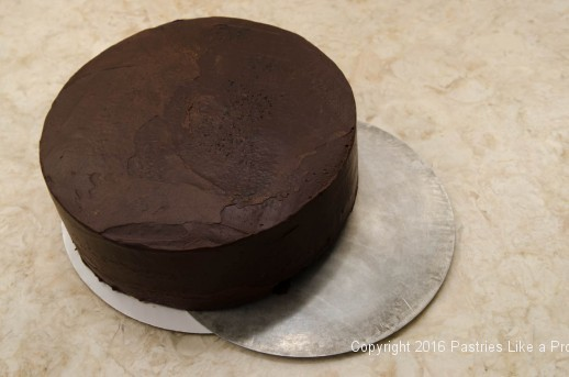 Cake being transferred to a metal round for the Chocolate Strawberry Ruffle Cake