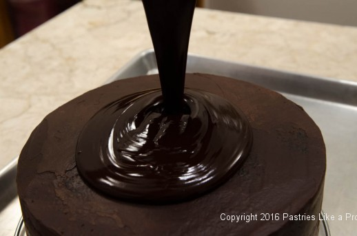 Pouring ganache on top of the cake for the Chocolate Strawberry Ruffle Cake