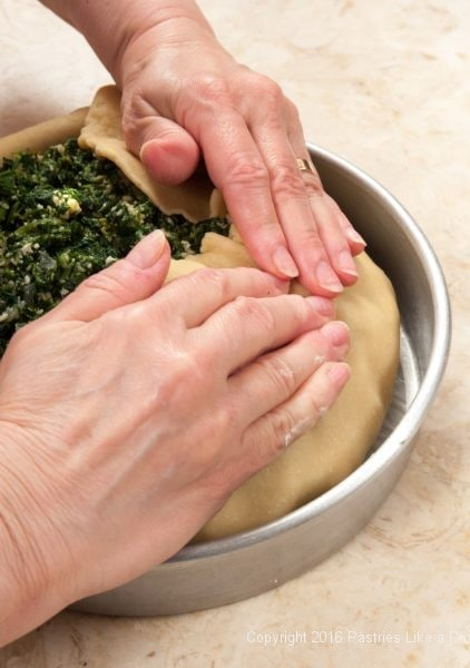 Pulling the edge of the dough into the center for the Torta Rustica
