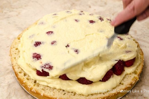 Raspberries topped with mascarpone filling for Tarte Tropezienne