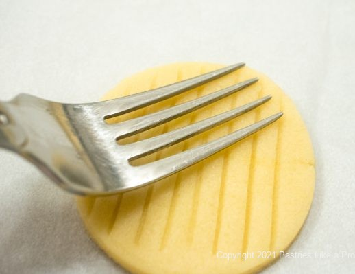 Fork making diagonal lines on top of pastry